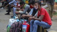 Für sie geht es nicht weiter: Die indischen Reisenden sind an einem Busbahnhof in Bengaluru gestrandet. Die Reichen fliegen mit ihren Jets in die Golfregion.
