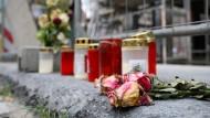 Blumen und Kerzen liegen unweit des Residenzschlosses vor einem Bauzaun an der Schlossstraße in Dresden.
