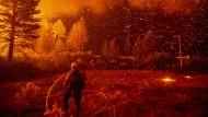 Glut fliegt über einen Feuerwehrmann, während er am im Shasta-Trinity National Forest in Kalifornien ein Feuer zu kontrollieren versucht.