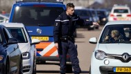 Ein Polizist schickt sogenannte Plane Spotters weg, die Flugzeuge am Flughafen Amsterdam Schiphol beobachten.