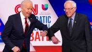 Joe Biden (links) und Bernie Sanders grüßen sich mit Ellebogen statt Händedruck auf einer Vorwahlkampfveranstaltung in Washington.
