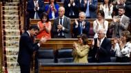 Auf der Suche nach einer Mehrheit: Sozialistische Abgeordnete applaudieren Ministerpräsident Sánchez  (l) am Montag nach seiner Wiederwahl.
