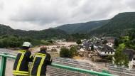 Feuerwehrmänner schauen über das überschwemmte Altenburg im Landkreis Ahrweiler.