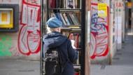 Mit Abstand und Handschuhen stöbern: Eine Frau am Bücherschrank am Frankfurter Merianplatz