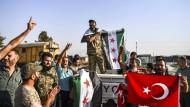 Syrische Oppositionskämpfer, die von der Türkei unterstützt werden, jubeln in Akcakale (Türkei), nachdem sie von Tall Abyad (Syrien) über die Grenze gekommen sind.