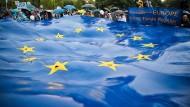 Rumänen halten eine große EU-Flagge bei einer Wahlkundgebung vor der Wahl des Europäischen Parlaments im Mai.