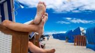 Ausspannen an Pfingsten: Urlauber sitzen mit nackten Füßen in einem Strandkorb am Ostseestrand in Warnemünde.