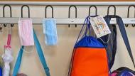 Masken hängen an Kleiderhaken in einer Grundschule in Bamberg.