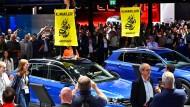 Greenpeace-Aktivisten stehen auf Volkswagen und protestieren auf der IAA