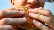 Ein Jugendlicher verzehrt einen Hamburger. (Symbolbild)