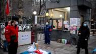 Anwohner und Wachleute führen am Eingang zu einem Wohnblock in Peking Ende Februar Corona-Kontrollen durch.