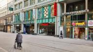 Tristesse statt buntem Treiben: Nur wenige Passanten sind noch in den Einkaufsstraßen wie hier in Hamburg unterwegs.