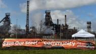 Das Banner einer Stahlgewerkschaft vor einem Stahlwerk in Wales