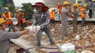 Rettungskräfte räumen Trümmer nach dem Einsturz des Rohbaus in Sihanoukville.