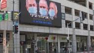 Eine elektronische Anzeigentafel in Ramat Gan zeigt Benjamin Netanjahu, Avigdor Lieberman und Benny Gantz mit Mundschutz