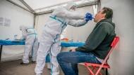 In einem Berliner Corona-Testzentrum lässt ein Mann einen Abstrich machen.