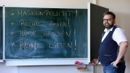 Der Direktor des Innerstädtischen Gymnasiums Rostock ISG, Markus Riemer, schlägt in einem Klassenzimmer eine Tafel mit den Corona-Verhaltensregeln auf.