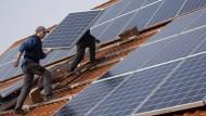 Monteure installieren eine Photovoltaik-Anlage auf dem Dach eines landwirtschaftlichen Gebäudes auf der Schwäbischen Alb. (Archivbild)