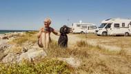 Die anderen sind auch schon alle da: Frau und Königspudel am Strand in der Normandie.