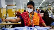 Eine Frau verarbeitet Textilien in Dhaka: Bangladeschs Textilverband fordert westliche Konzerne zur Fairness auf. In der Corona-Krise haben einige Unternehmen versucht, Nachlässe zu verlangen und sich um das Zahlen ihrer Rechnungen gedrückt.