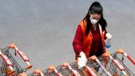 Die Mitarbeiterin eines Lebensmittelgeschäftes in Wien desinfiziert Einkaufswagen.
