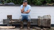 Wolfgang Ewerts aus Rheinland-Pfalz sitzt gegenüber seines von der Flutkatastrophe völlig zerstörten Hotels auf einem steinernen Betstock.