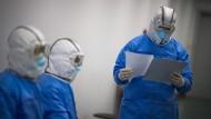 Wuhan und die Bilder des neuen Alltags: Medizinische Mitarbeiter mit Atemmasken und Schutzanzügen.