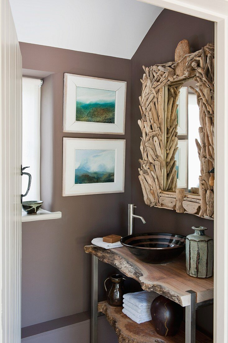 https www living4media com images 11167362 rustic washstand under bathroom mirror with artistic driftwood frame two modern watercolour landscapes on wall