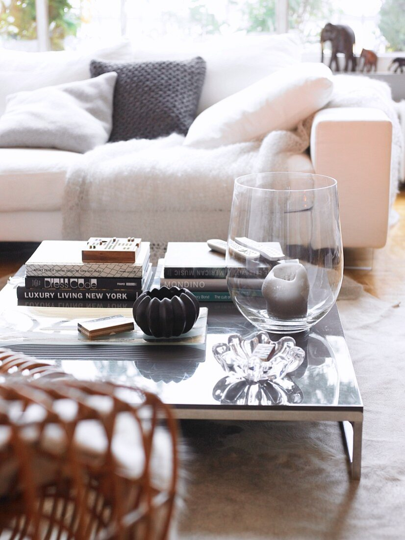 https www living4media com images 11252768 candle in large glass vase and stacked books on low coffee table in front of white couch with scatter cushions