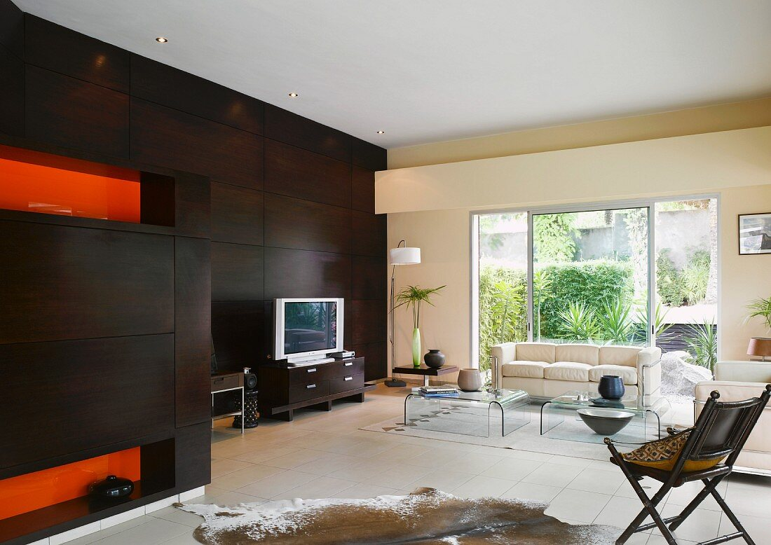 https www living4media com images 11014036 modern living room with dark wooden wall animal skin rug and acrylic glass coffee tables