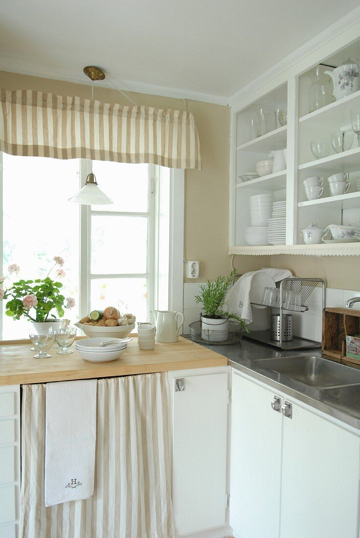https www living4media com images 11017494 corner of kitchen counter below window and white crockery cabinet above sink