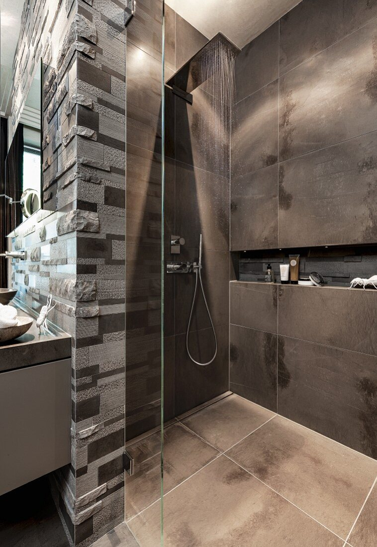 http www living4media com images 11328798 an open rain shower with dark tiles and a glass partition wall with limestone relief tiles behind the sink