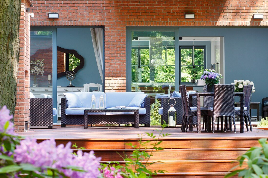 https www living4media com images 11344028 dark modern wicker outdoor furniture on wooden deck in front of house with grey painted window frames and wall