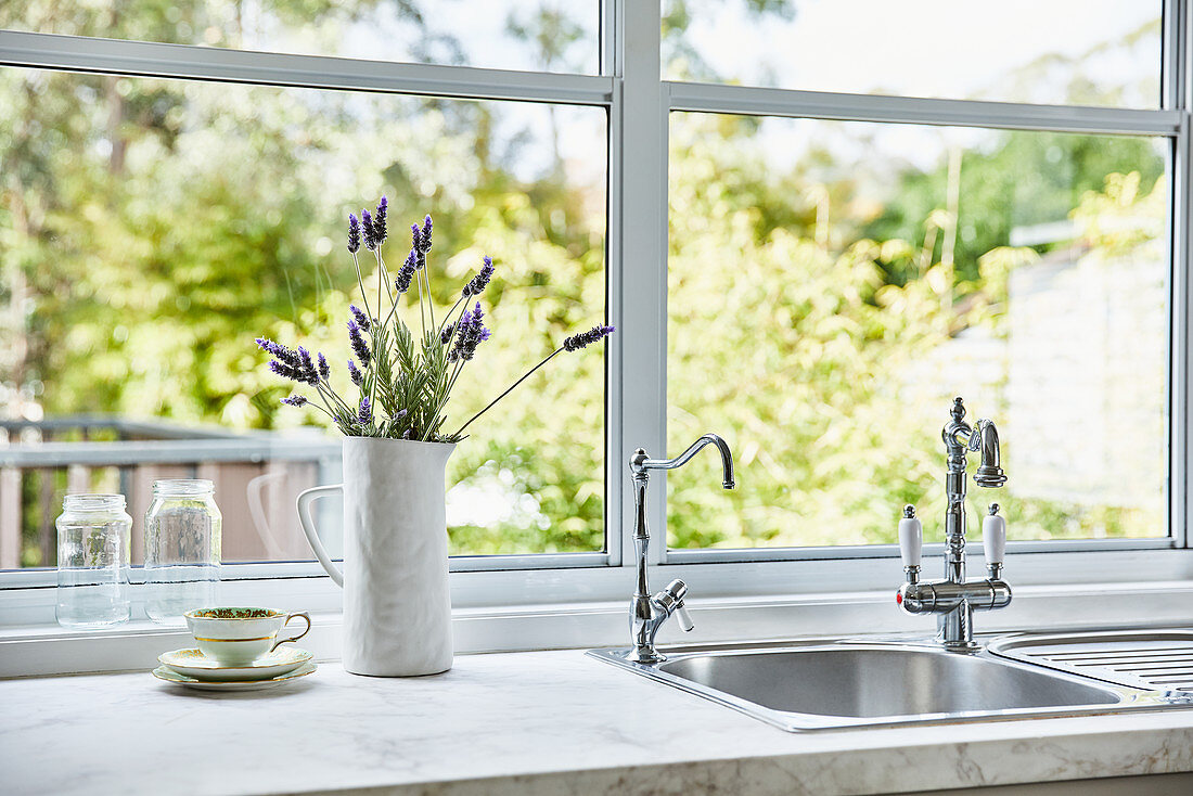 https www living4media com images 12507692 jug of lavender flowers next to sink integrated in kitchen counter below window
