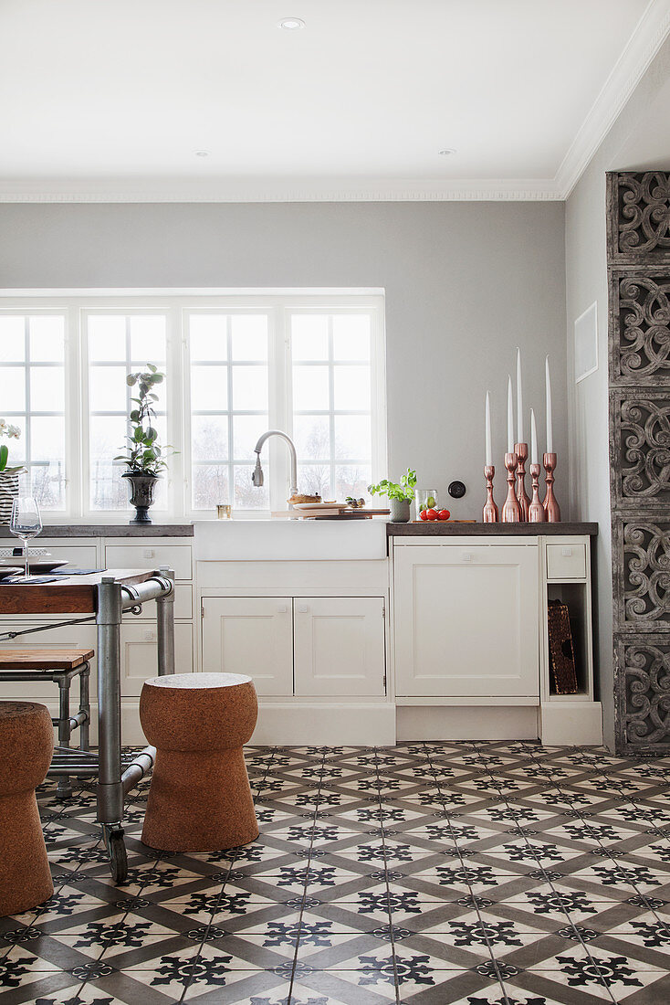 https www stockfood com images 13177120 a vintage dining table and cork shaped stools in a country house kitchen with decorative floor tiles