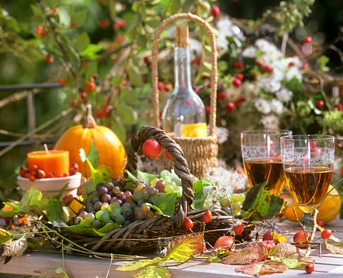 Jesenski ukras: košarica vinove loze, lišća, svijeća, čaša