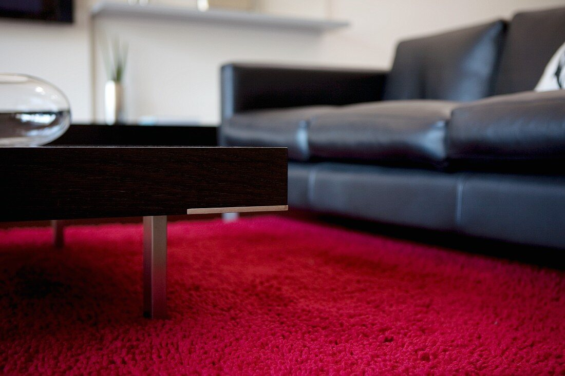 https www living4media com images 11225601 black leather couch and coffee table with metal legs on red carpet