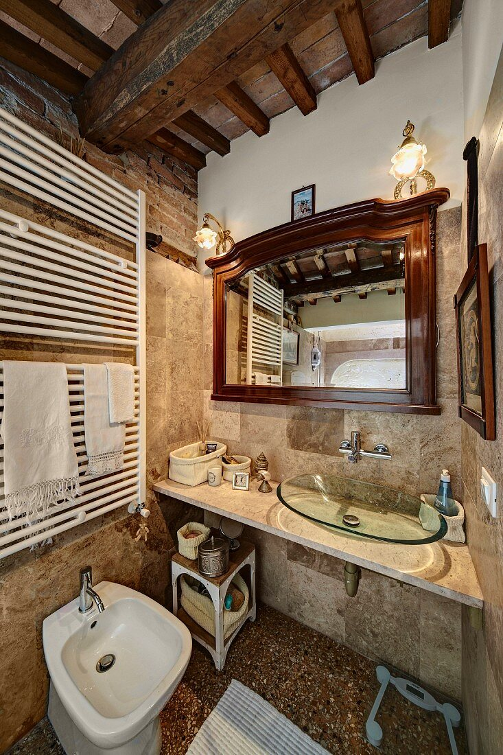 https www living4media com images 11394765 rustic bathroom with wood beamed ceiling washstand with modern glass basin and white heated towel rail above