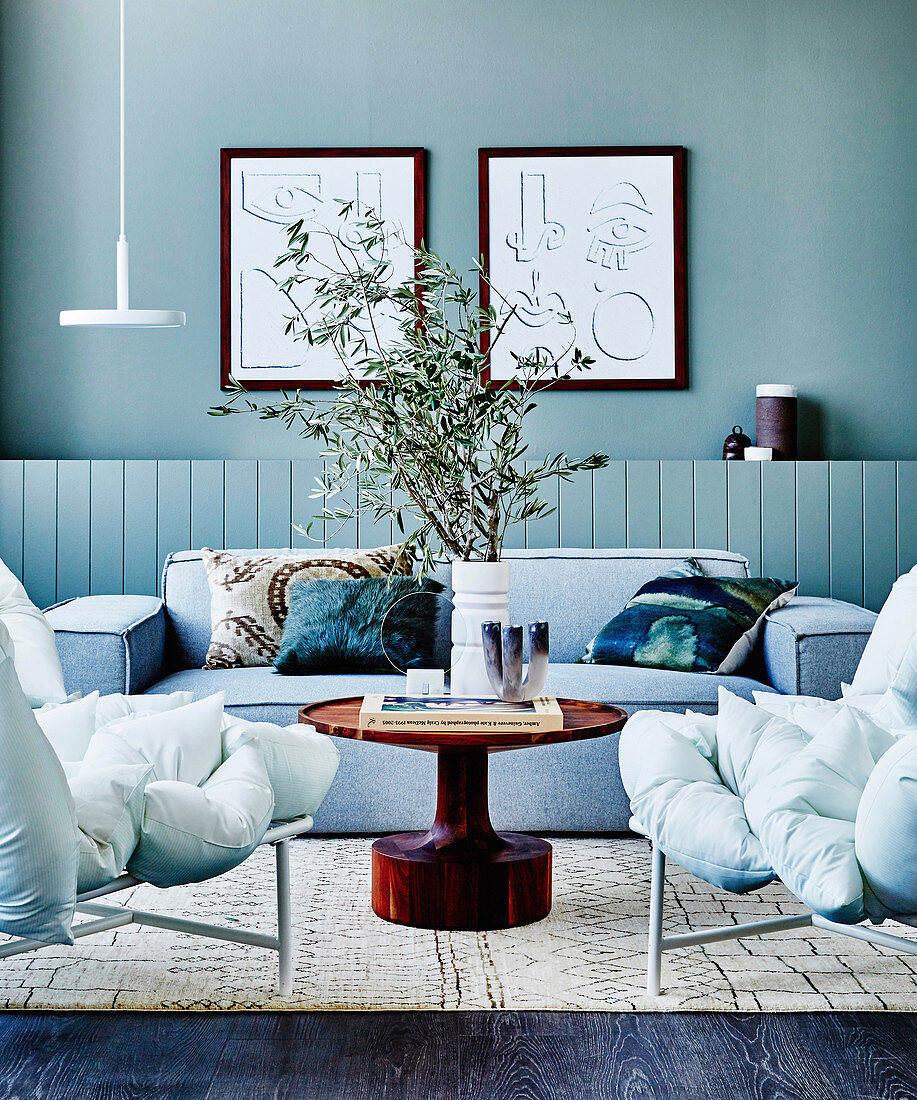 https www living4media com images 12429467 gray upholstered sofa round coffee table and split cushion sofa in the living room with gray green wall