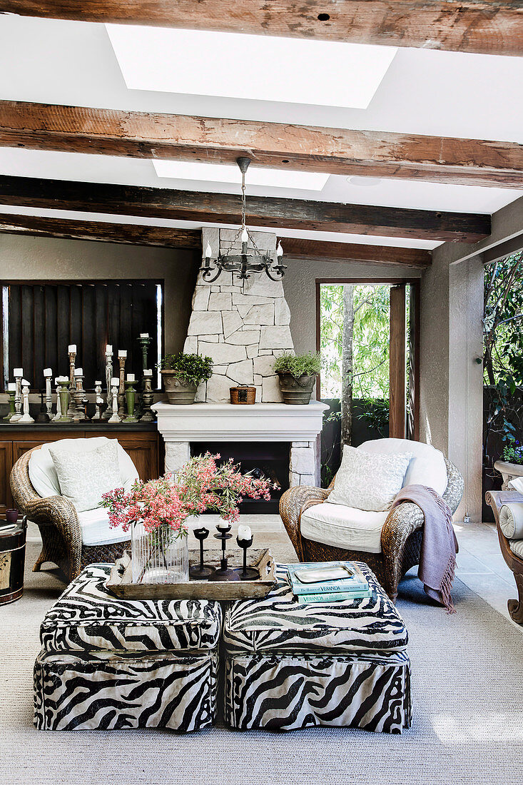 https www living4media com images 12501593 rattan armchairs and ottoman with animal print in front of fireplace on living terrace
