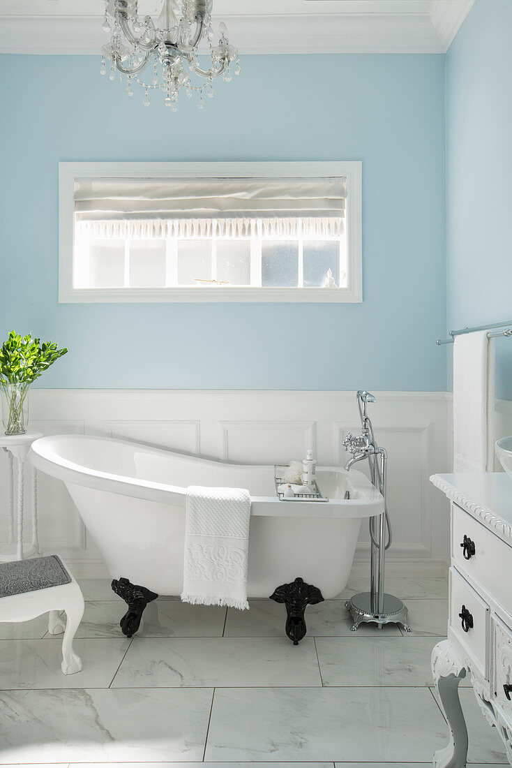 https www living4media com images 12547773 free standing bathtub in bright bathroom with pale blue walls and marble tiles