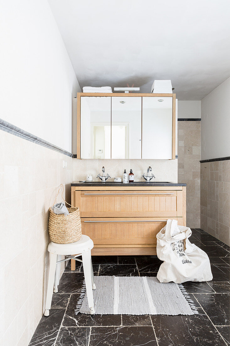 https www living4media com images 12375007 washstand with wooden fronts below mirror wall cabinet in bathroom with black marble floor tiles