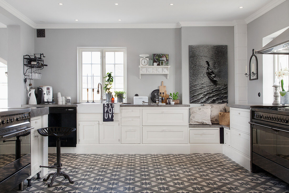 https www stockfood com images 13177119 a spacious country house kitchen in black white and grey with decorative floor tiles