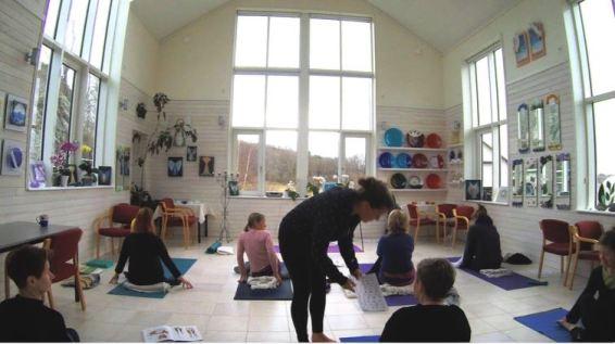 Bilden viser yoga studion på Koster med eleverna och yogalärare Miriam. Ljuset kommer in genom de stora fönsterna.