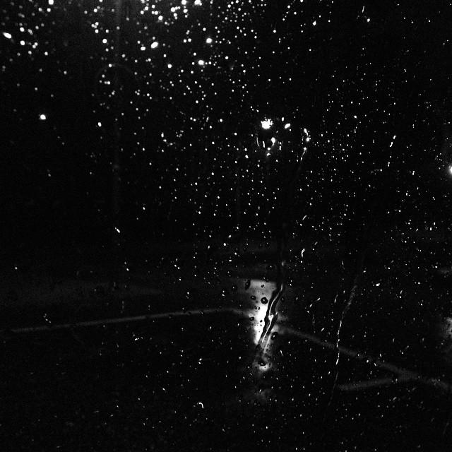 Sitter i bilen och väntar på Maria. Regnet öser ner.