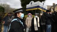 Eine Polizistin und Demonstranten vor der Batley Grammar School in Battley, West Yorkshire, am Freitag