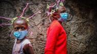 Zwei Mädchen in Nairobi tragen bunte Zöpfe und Schutzmasken, um Aufmerksamkeit für das Coronavirus zu erzeugen.