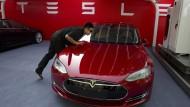Ein Arbeiter putzt ein Tesla Model S vor einer Präsentation in Peking.