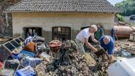 """In der ehemaligen Gaststätte """"Eifelstube"""" in der Sahrstraße räumen Helfer zerstörte Dinge aus dem Haus."""