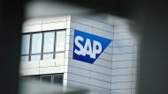 Ein Firmenlogo des Softwarekonzerns SAP ist an einem Firmengebäude angebracht.